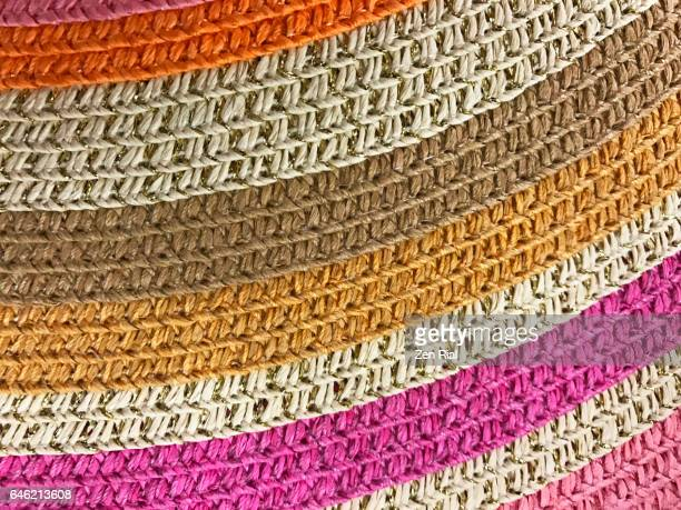 Close-up of a multi colored brim of a straw hat shows curves of the woven material