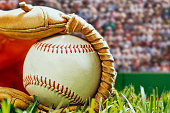 A low angle close-up of a new baseball sitting in a brown leather baseball glove that is lying in the grass with a stadium full of spectators in the background with any over all grainy look.