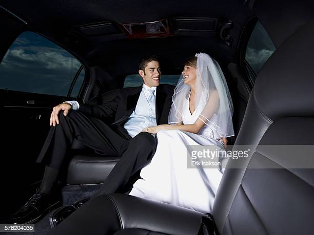 Close-up of a newlywed couple sitting in a car and looking at each other