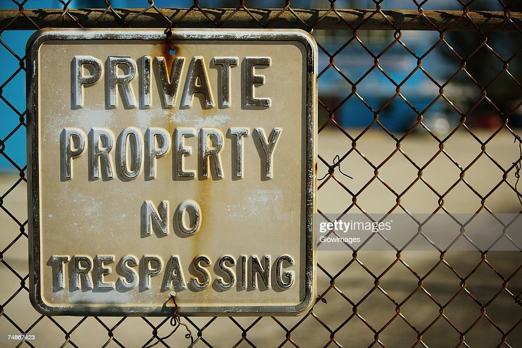 Close-up of a no trespassing sign on a chain-link fence