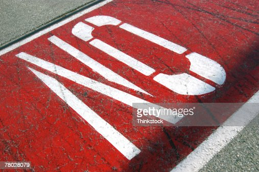 Close-up of a painted sign reading NO on pavement. : Stock Photo