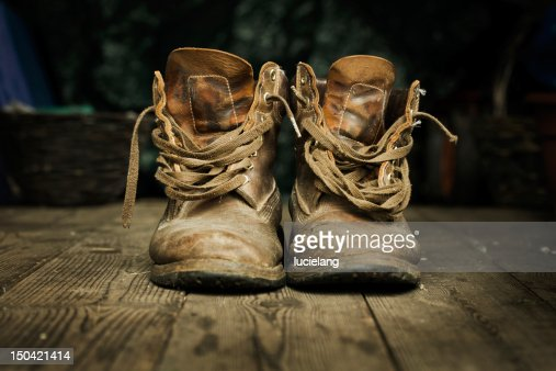 Close-up of a pair of old brown boots on a wooden floor : Stock Photo