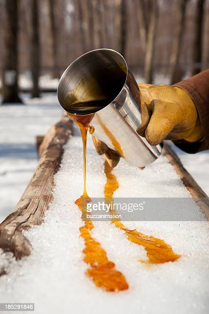 A close-up of a person pouring maple syrup onto snow