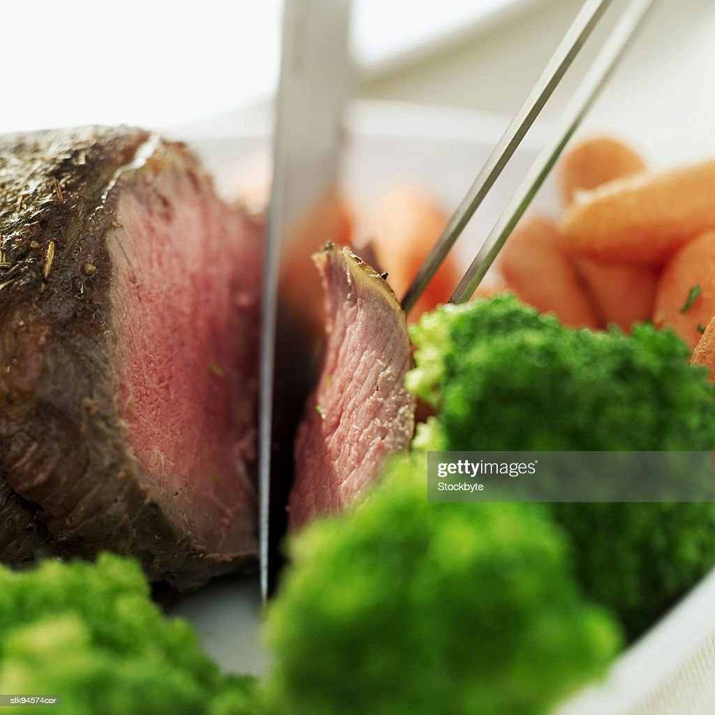 close-up of a person slicing a meat loaf : Stock Photo