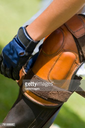 Close-up of a person tying a riding boot : Stock Photo