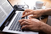 Person's Hand Typing On Laptop Over Wooden Desk