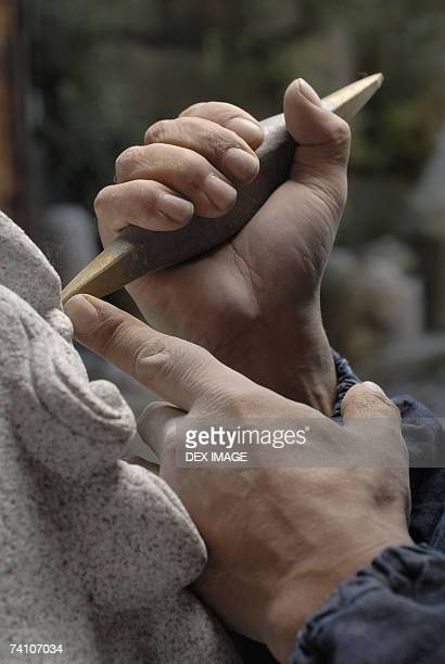 Close-up of a person's hand carving a statue with a chisel