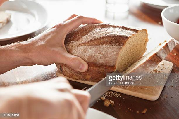 Close-up of a person's hand cutting bread