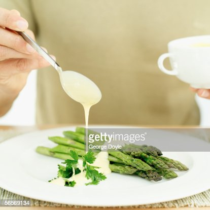 close-up of a person's hand dressing stalks of asparagus with cream