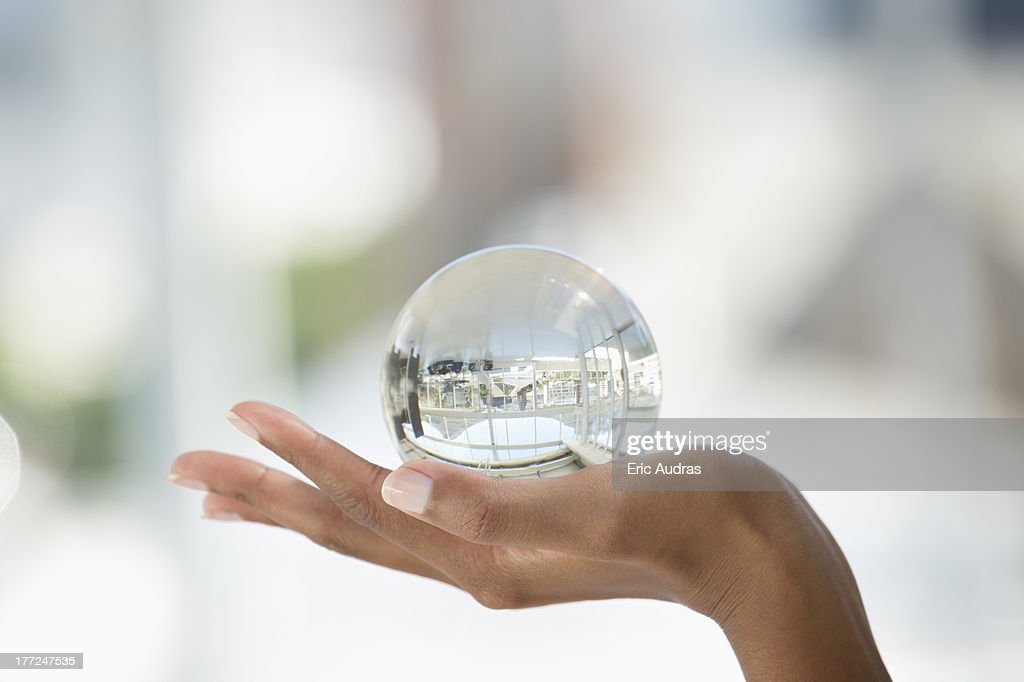 Close-up of a person's hand holding a crystal ball : Stock Photo
