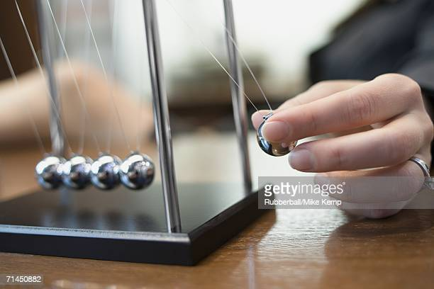 Close-up of a person's hand holding a pendulum