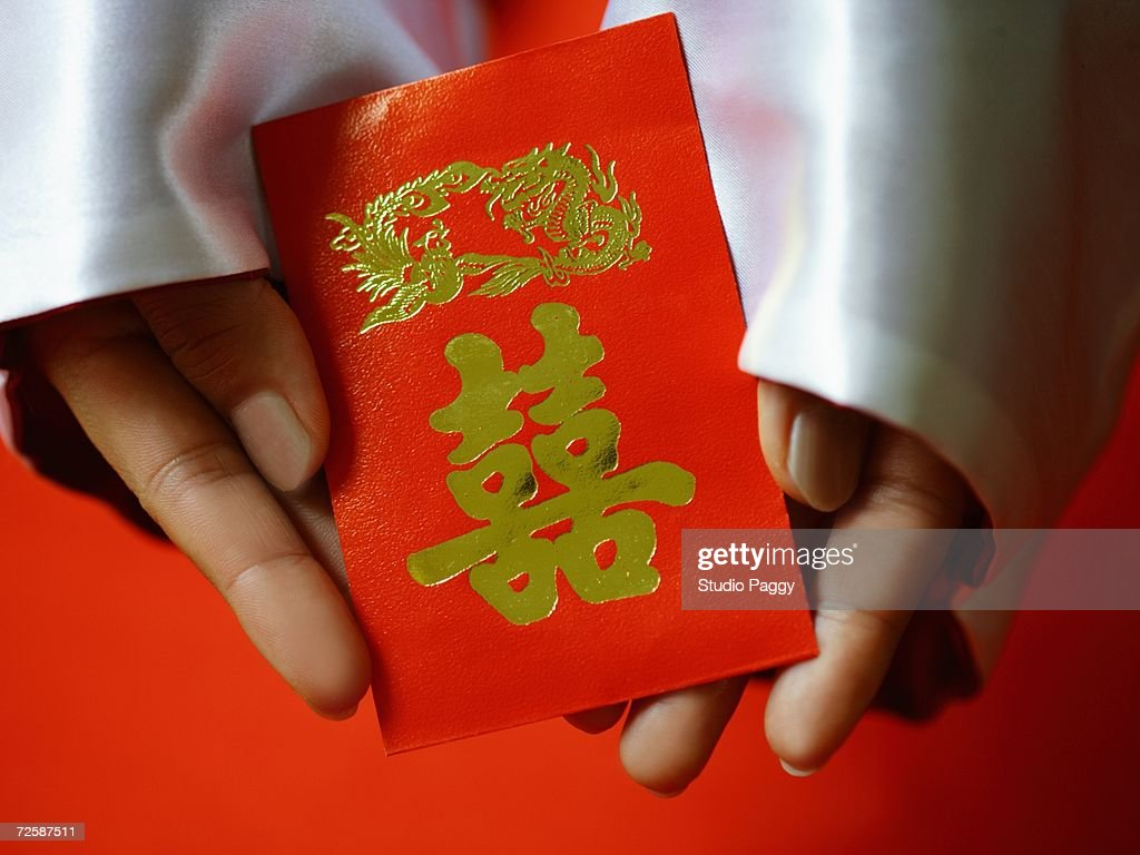 Closeup of a persons hand holding a red gift packet stock photo close up of a persons hand holding a red gift packet hong bao negle Choice Image