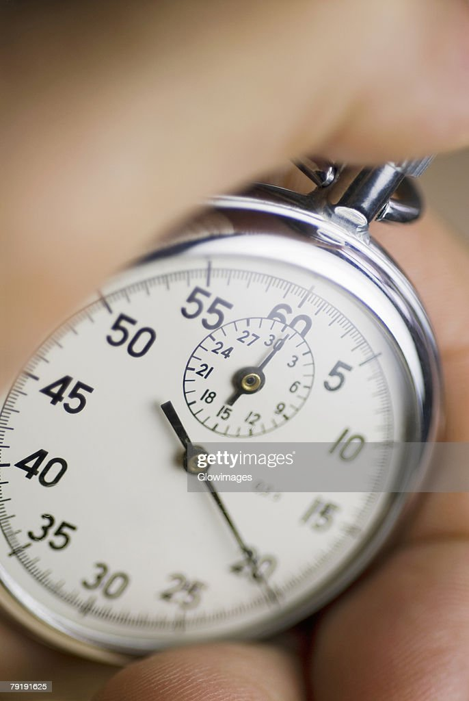 Close-up of a person's hand holding a stopwatch : Foto de stock