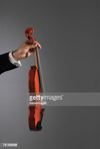 Close-up of a person's hand holding a violin : Foto de stock