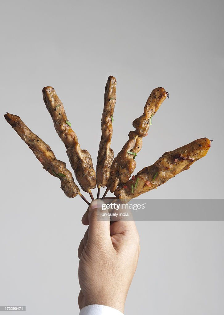 Close-up of a person's hand holding kebabs : Stock Photo
