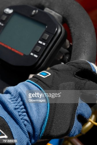 Close-up of a person's hand on the steering wheel of a racecar : Foto de stock