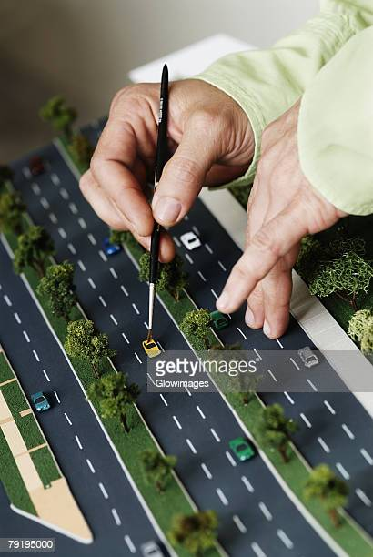 Close-up of a person's hand placing a car on a model of highway