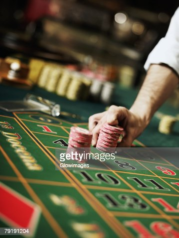 Close-up of a person's hand placing gambling chips on a gambling table : Foto de stock