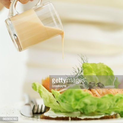 close-up of a person's hand pouring a jug of salad dressing over a sushi salad