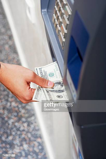 Close-up of a person's hand receiving one hundred dollar bills from an ATM