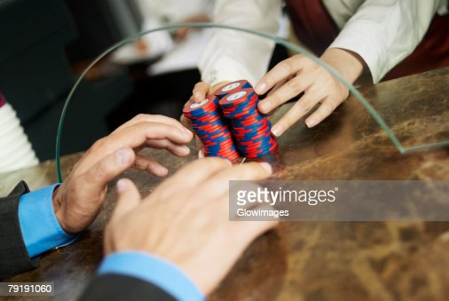 Close-up of a person's hand taking gambling chips from the checkout counter of a casino : Foto de stock