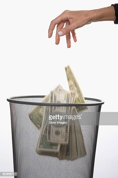 Close-up of a person's hand throwing US dollar bills in a garbage bin