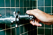 Close-up of a person's hand turning a shower knob