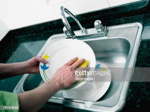 Close-up of a person's hand washing plate in the kitchen : Stock Photo
