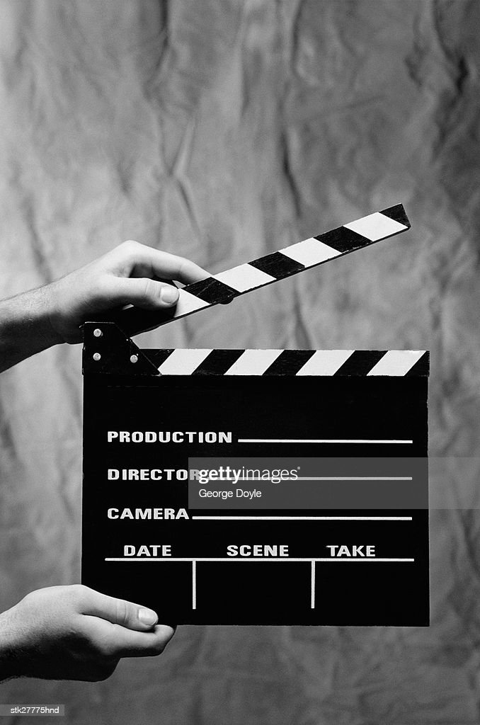 Close-up of a person's hands holding a clapperboard (black and white) : Stock Photo