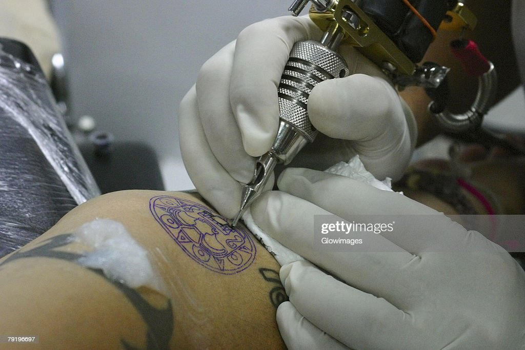 Close-up of a person's hands tattooing on a person's arm, Bangkok, Thailand : Stock Photo