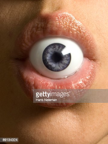 Close-up of a person's mouth holding a plastic eye, Buenos Aires, Argentina