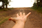 Close-up of a person's palm extended toward a dirt road, La Pampa, Argentina