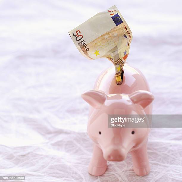 Close-up of a piggy bank with one fifty euro note sticking out of top