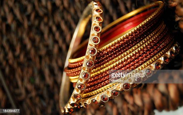 Close-up of a pile of red and gold bangles