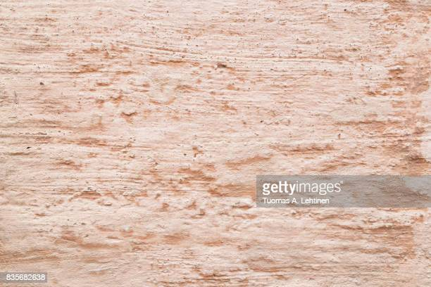Close-up of a plastered wall in pale and bleached red or peach color.
