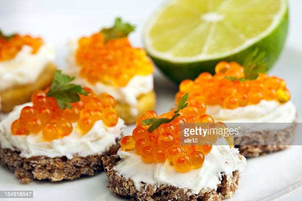 Close-up of a plate of garnished caviar appetizers with lime