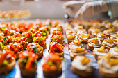 Closeup of a tray with rows of colored and delicious canapes. Chef arranging them in the background.