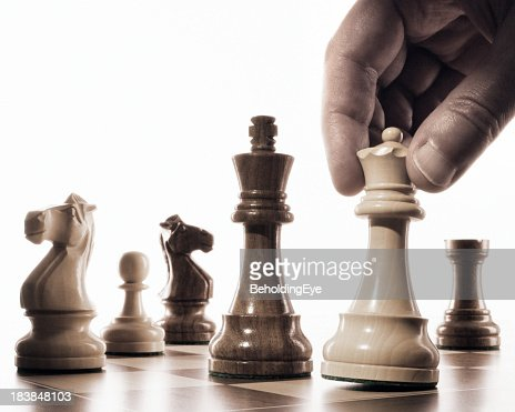 Close-up of a player moving the white queen into checkmate