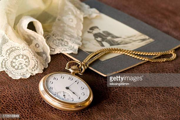 Close-up of a pocket watch, vintage photo and handkerchief