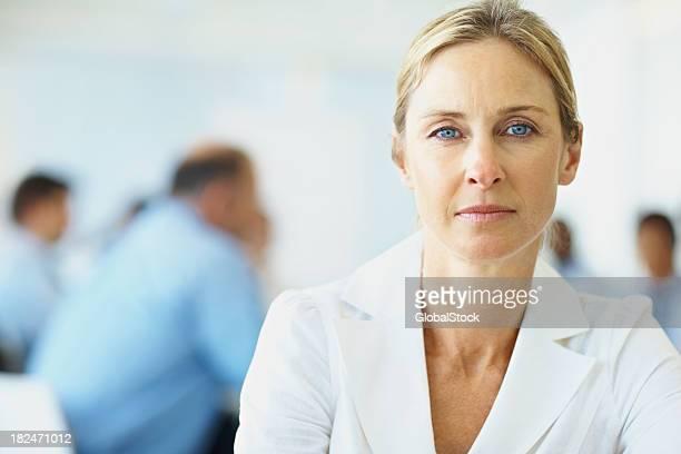 Primer plano de una hermosa mujer con las personas de negocios, en el fondo