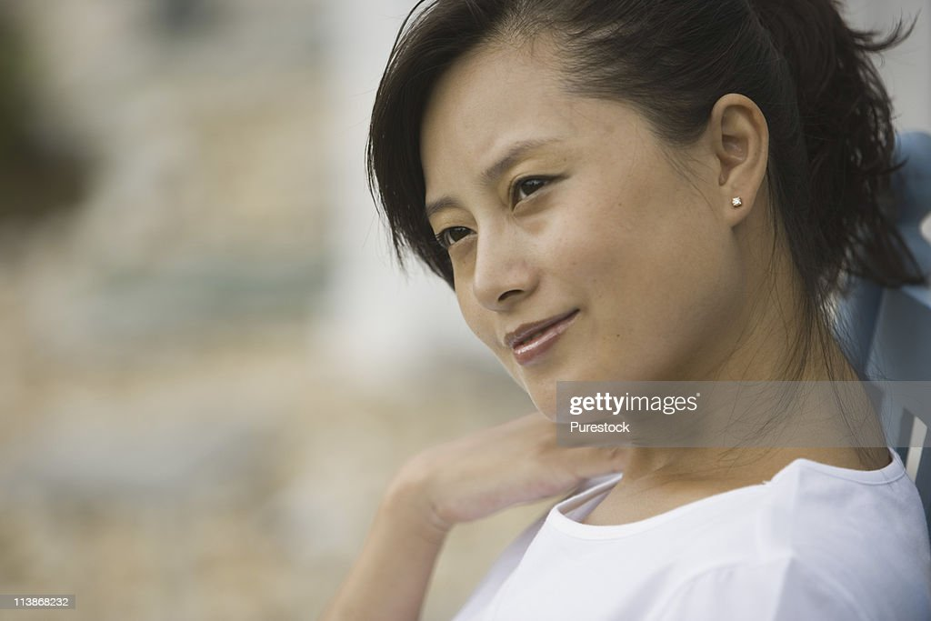Close-up of a pretty young Asian woman smiling : Stock Photo