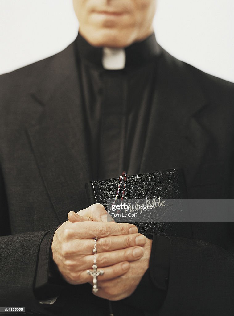 Close-Up of a Priest Holding Rosary Beads and a Bible in Prayer