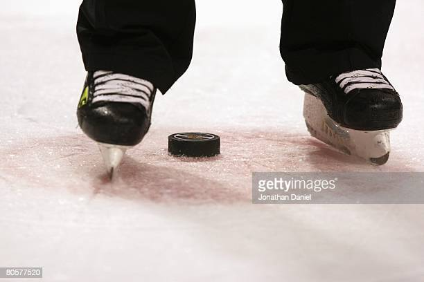 A closeup of a referee's skates and a puck on the faceoff circle during the NHL game between the Chicago Blackhawks and the Detroit Red Wings on...