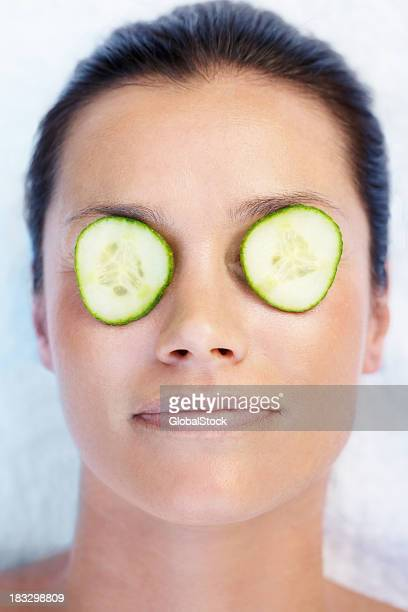 Closeup of a relaxed woman with cucumber slices over eyes