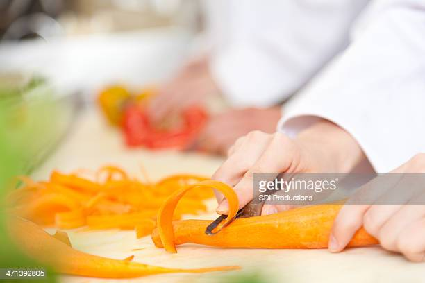 Closeup of a restaurant cook cutting carrots into slices