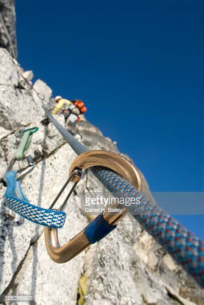 Closeup of a rock climbing carabiner and climber on a rocky mountainside