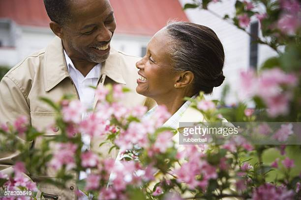 Close-up of a senior man and a senior woman smiling behind flowers