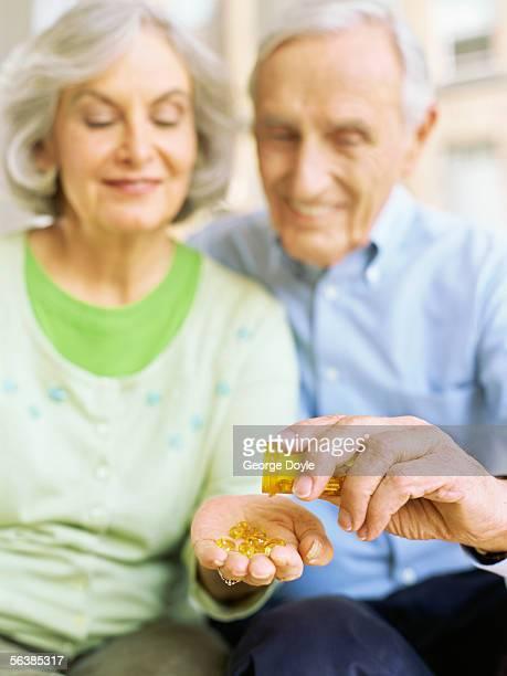 close-up of a senior man giving pills to a senior woman