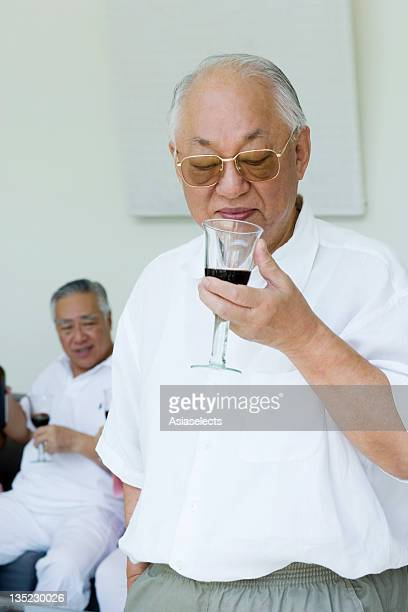 Close-up of a senior man holding a wine glass with his friend in the background