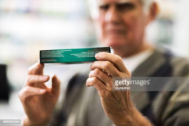 Close-up of a senior man holding medicine.